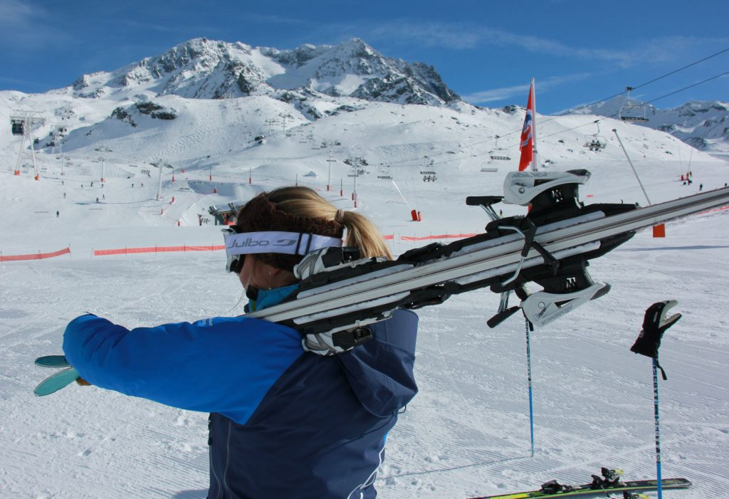 Carrying skis over shoulder view from behind